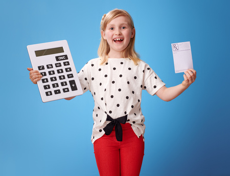 smiling modern child in red pants showing prescription and calculator against blue background