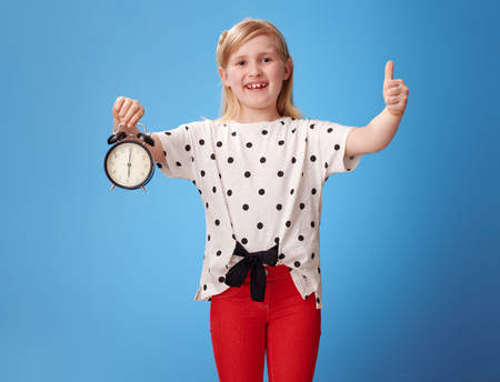 happy modern child in red pants with alarm clock showing thumbs up against blue background
