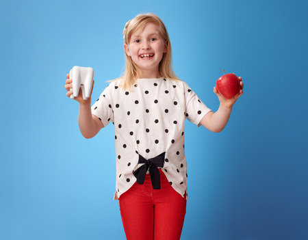happy modern girl in red pants showing tooth and an apple isolated on blue