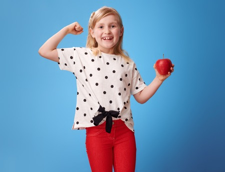 smiling modern child in red pants with an apple showing biceps against blue background