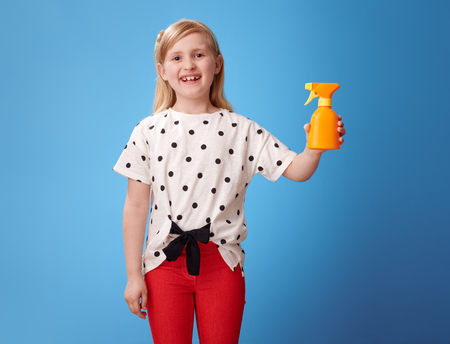 happy modern girl in red pants showing sun cream on blue background Stock Photo