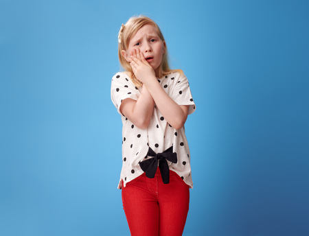 sad modern girl in red pants with a toothache against blue background