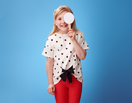 smiling modern child in red pants with covered one eye taking the visual acuity test against blue background Stockfoto
