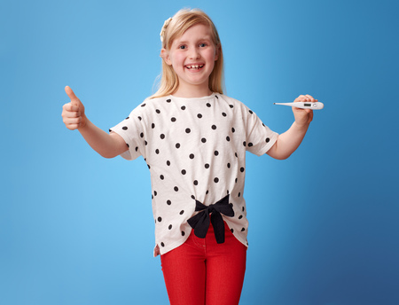 smiling modern girl in red pants showing thumbs up and thermometer against blue background