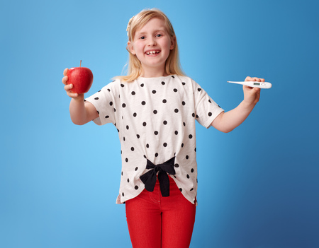 smiling modern child in red pants showing an apple and a thermometer on blue background Stock Photo