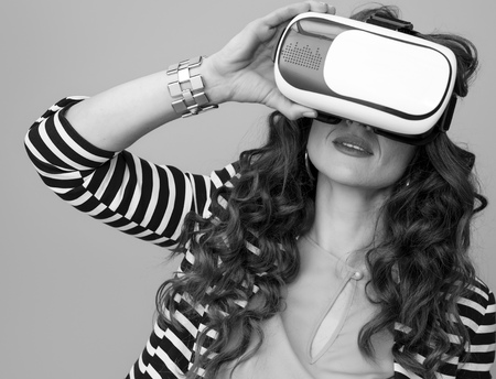 trendy woman in striped jacket against background in VR headset Stok Fotoğraf - 102614044
