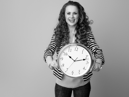 smiling trendy woman with long wavy brunette hair on background showing clock