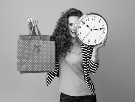 smiling young woman with long wavy brunette hair against background with clock and shopping bags
