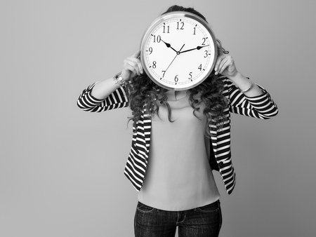 young woman in striped jacket isolated on background holding clock in the front of face