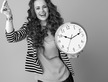 happy modern woman with long wavy brunette hair on background with clock snapping fingers Stock Photo