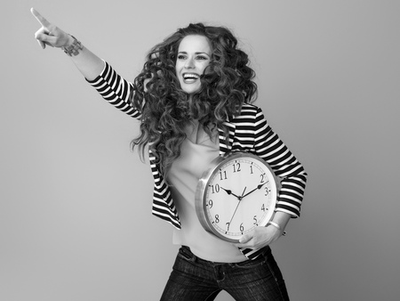 happy stylish woman with long wavy brunette hair isolated on background with clock pointing at something Stock Photo