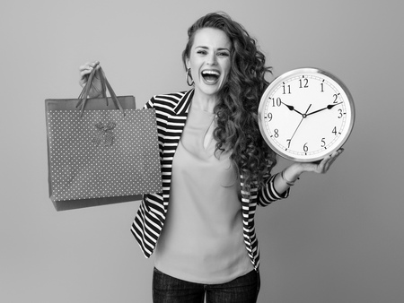smiling trendy woman with long wavy brunette hair on background showing clock and shopping bags