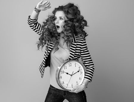 surprised stylish woman in striped jacket isolated on background with clock looking into the distance 版權商用圖片