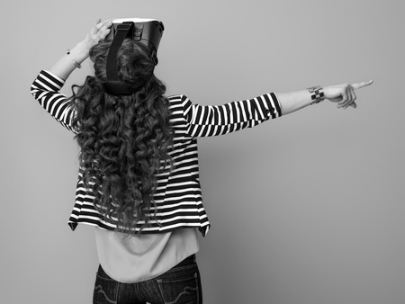 Seen from behind trendy woman with long wavy brunette hair isolated on background in VR headset pointing at something