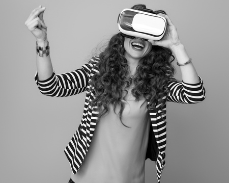happy stylish woman with long wavy brunette hair against background using virtual reality gear and snapping fingers Stock Photo