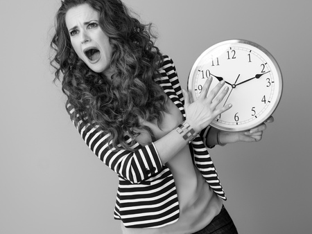 sad stylish woman in striped jacket on background with clock