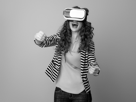 smiling stylish woman with long wavy brunette hair isolated on wearing cardboard VR glasses and driving 스톡 콘텐츠