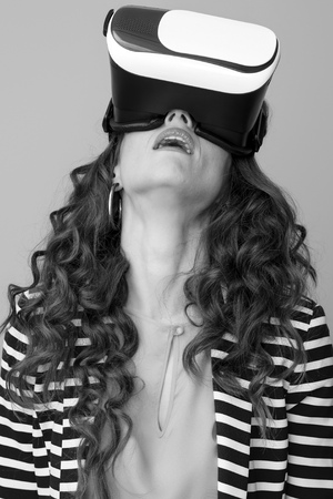 tired young woman with long wavy brunette hair isolated on wearing virtual reality headset Stok Fotoğraf