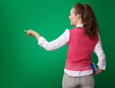Seen from behind young student woman in a red waistcoat with a blue notebook pointing at something on green background Stock Photo