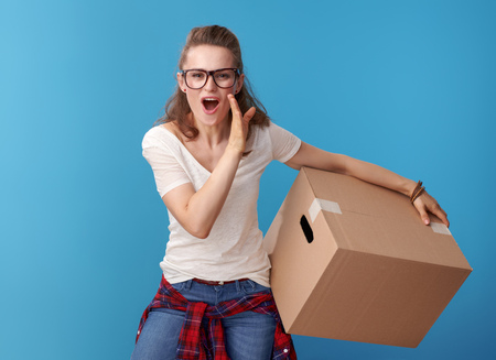 happy modern woman in white shirt with a cardboard box telling exciting news isolated on blue