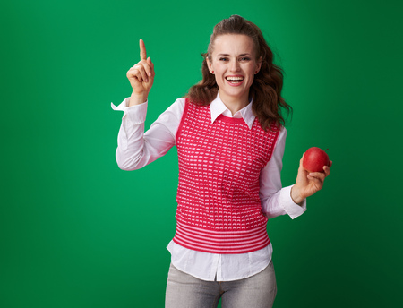 smiling modern student woman in a red waistcoat with an apple got idea on green background