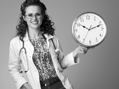 smiling paediatrician doctor in white medical robe showing clock isolated on Stock Photo