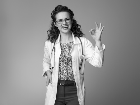 smiling pediatrist woman in white medical robe showing ok gesture isolated on