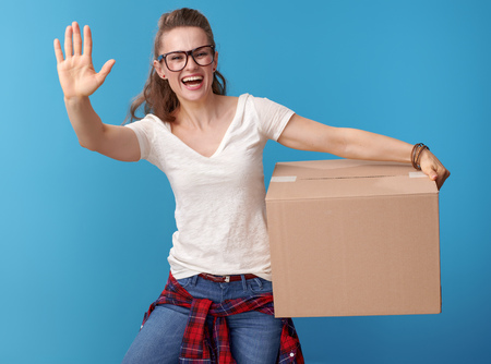 smiling young woman in white shirt with a cardboard box greeting against blue background Banque d'images - 103360790