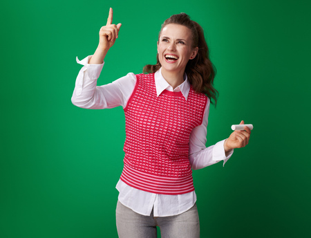 smiling young student woman in a red waistcoat with a piece of chalk got idea on green background