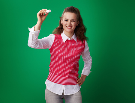 smiling modern student woman in a red waistcoat writing with a piece of chalk on green background