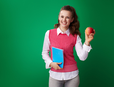 smiling young student woman in a red waistcoat with a blue notebook showing an apple on green background Stock Photo