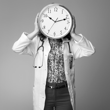 paediatrist woman in white medical robe holding clock in the front of face isolated on