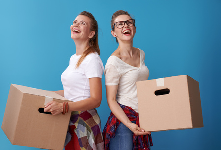 happy modern female friends in white shirts holding a cardboard boxes and looking up at copy space isolated on blue 版權商用圖片