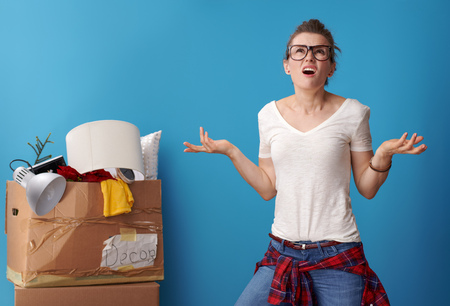unhappy active woman in white shirt with an untidy cardboard box in the background looking up on blue