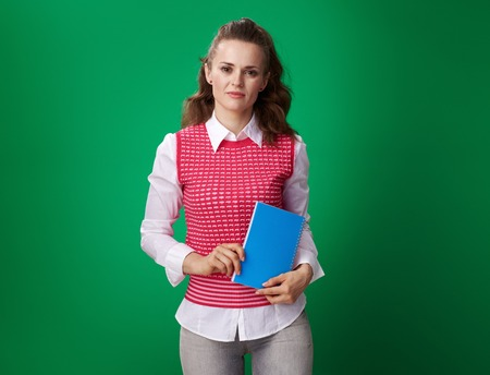 Portrait of modern student woman in a red waistcoat with a blue notebook isolated on green background