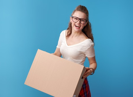 Portrait of cheerful active hipster in white shirt with a cardboard box isolated on blue background