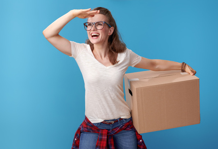 happy young woman in white shirt with a cardboard box looking into the distance on blue background