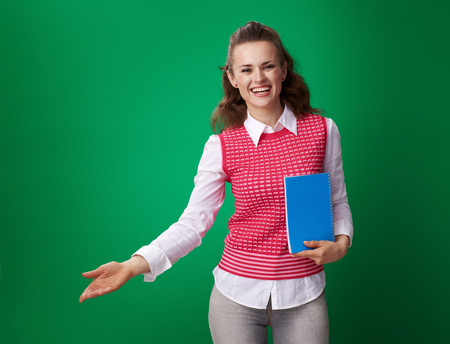 smiling modern student woman in a red waistcoat with a blue notebook welcoming against green background Banque d'images - 103360880