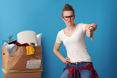 sad young woman in white shirt showing thumbs down and an untidy cardboard box in the background isolated on blue Stock Photo