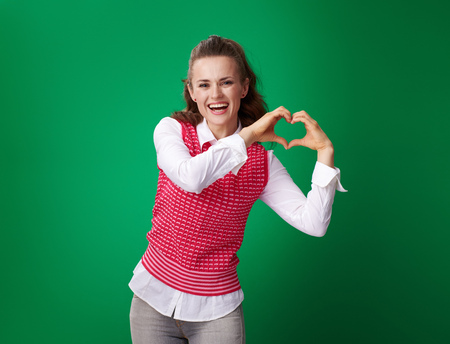 smiling modern student woman in a red waistcoat showing heart shaped hands on green background