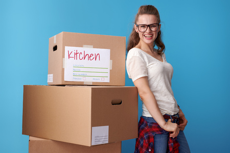 Portrait of happy modern woman in white shirt standing next to the cardboard boxes isolated on blue background Stockfoto