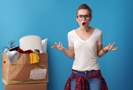 shocked modern woman in white shirt with an untidy cardboard box in the background isolated on blue