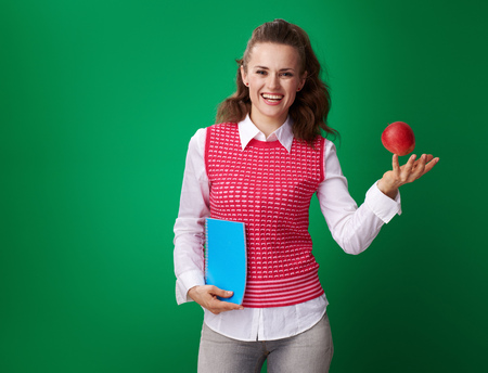 smiling young student woman in a red waistcoat with a blue notebook throwing an apple up on green background