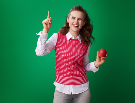 happy young student woman in a red waistcoat with an apple got idea isolated on green