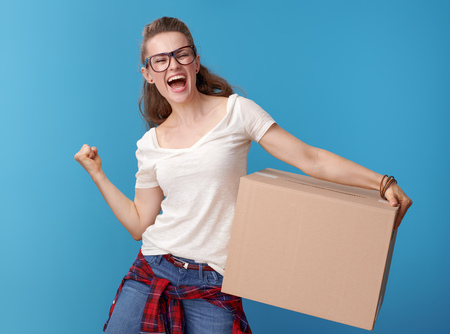 happy young woman in white shirt with a cardboard box rejoicing on blue background