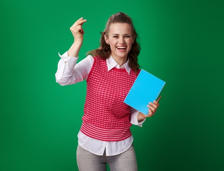 happy young student woman in a red waistcoat with a blue notebook fingers snapping isolated on green Stock Photo