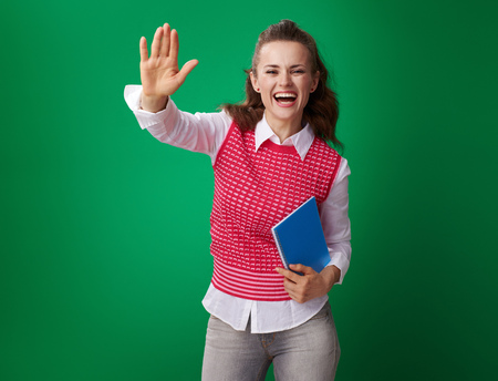 happy modern student woman in a red waistcoat with a blue notebook high five on green background Stock Photo - 103329924