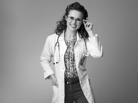 Portrait of happy paediatrician doctor in white medical robe correcting glasses on background