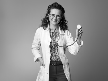 happy paediatrist woman in white medical robe using a stethoscope isolated on Stock Photo