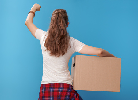 Seen from behind modern woman in white shirt with a cardboard box rejoicing against blue background 스톡 콘텐츠